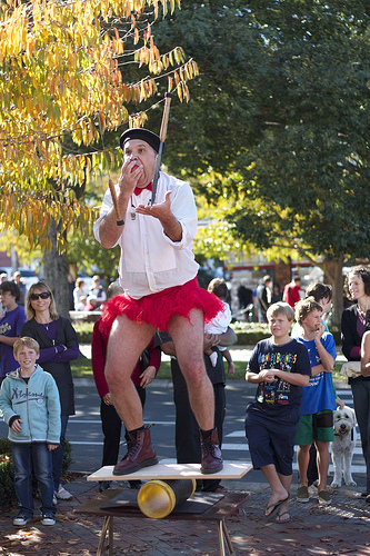 Eating an apple, while juggling knives, while balancing on a board on a drum on a table, while performing a comedy act, while wearing a tutu. Whew! Busy or fulfilled?