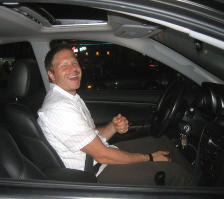 He's happy. He got the loan, and now has the car. Will he still be smiling after he gets done with the insurance paperwork? Did he think ahead, or was he a little stupid?